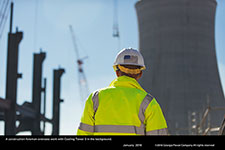 A construction foreman oversees work with Cooling Tower 3 in the background.