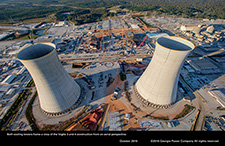 Both cooling towers frame a view of the Vogtle 3 and 4 construction from an aerial perspective.