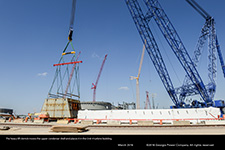 The heavy lift derrick begins to move the upper condenser shell for the Unit 4 turbine building.