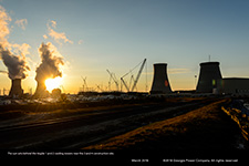 The sun sets behind the Vogtle 1 and 2 cooling towers near the 3 and 4 construction site.