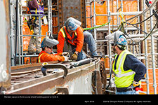 Workers secure a third course shield building panel on Unit 3.