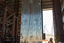 A sub-module wall section being lifted inside the Module Assembly Building.