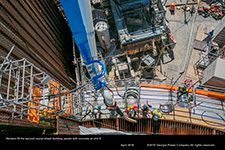 Workers fill the second course shield building panels with concrete at Unit 3.