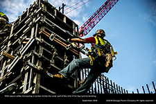With secure safety harnessing, a worker climbs the outer wall of the Unit 3 first bay turbine building.