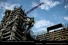 With a crane reaching skyward, workers scale the Unit 3 first bay turbine building.