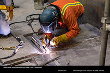 Vogtle worker welds together floor liner plates in Unit 3 containment.