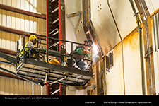Workers weld a section of the Unit 4 CA01 structural module.