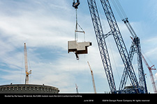 Guided by the heavy lift derrick, the CA05 module nears the Unit 4 containment building.