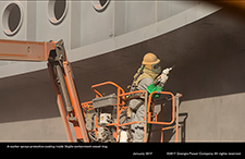 A worker sprays protective coating inside Vogtle containment vessel ring.