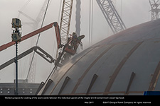 Workers prepare for coating of the seam welds between the individual panels of the Vogtle Unit 3 containment vessel top head.