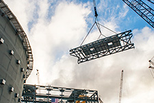 The heavy lift derrick guides the final roof truss toward the Unit 3 turbine building.
