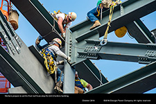 Workers prepare to set the final roof truss atop the Unit 3 turbine building.