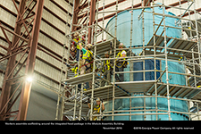 Workers assemble scaffolding around the integrated head package in the Module Assembly Building